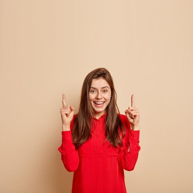 기뻐하는 아름다운 젊은 여성이 위쪽을 가리키고, 인상적이고 매혹적이며, 빨간색 세련된 셔츠를 입고, 베이지 색 벽에 아이템을 시연하고, 프로모션을위한 빈 공간을 보여줍니다. 무료 사진