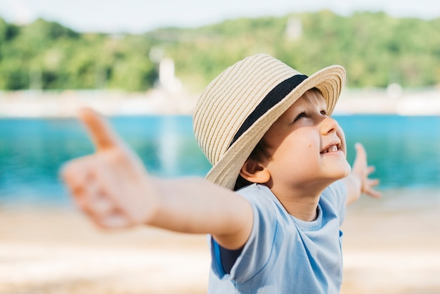 Delighted boy spreading hands and looking up in daylight Free Photo