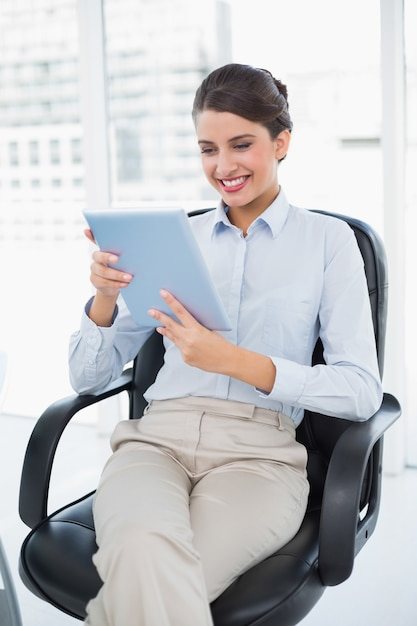 Delighted classy brown haired businesswoman using a tablet pc Premium Photo