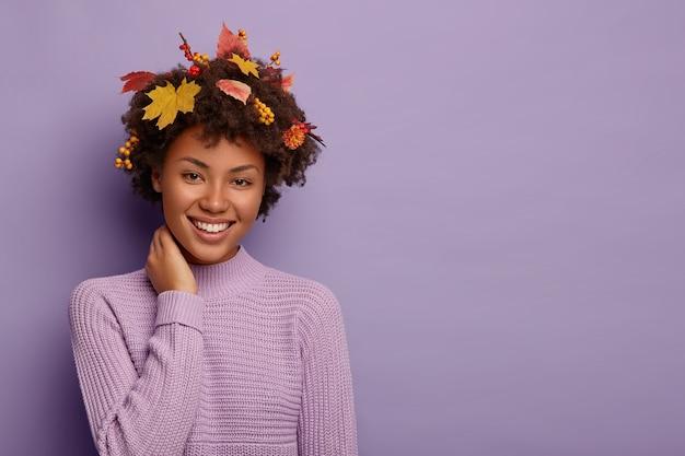 Felice ragazza etnica esprime emozioni sincere, tocca il collo e ridacchia felicemente, vestita con un caldo maglione lavorato a maglia, guarda con un ampio sorriso, ha un'acconciatura con foglie gialle Foto Gratuite
