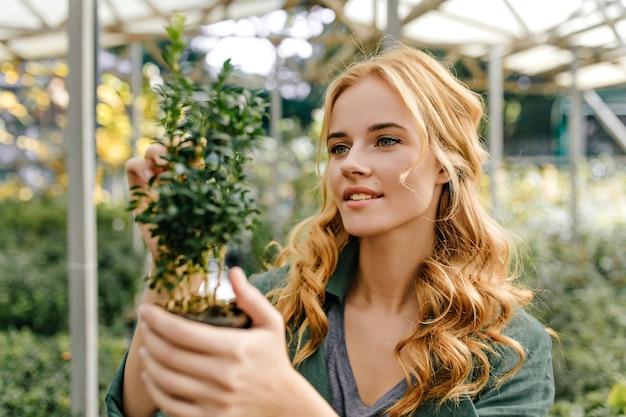 喜んで、探検家は植物の構造を研究します。肖像画のポーズをとって緑のトップかわいい笑顔の若い女性。 無料写真