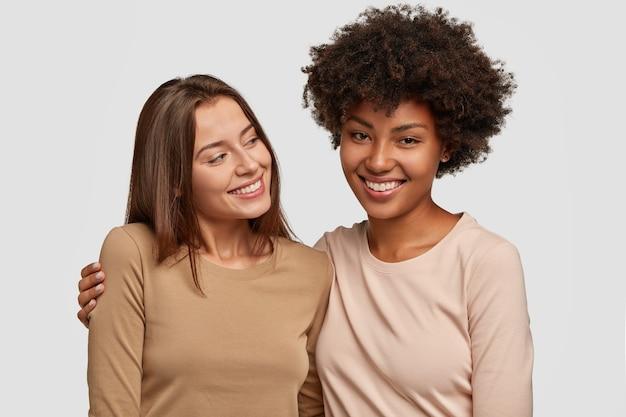 흰 벽에 포즈를 취하는 기쁘게 행복 한 여자 친구 무료 사진