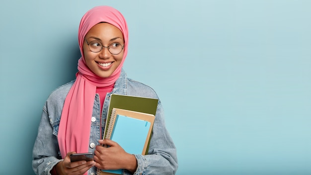 Delighted happy muslim student types messages on cell phone, carries notepad, focused aside with joyful expression, wears jean jacket, isolated against blue wall, reads interesting article Free Photo