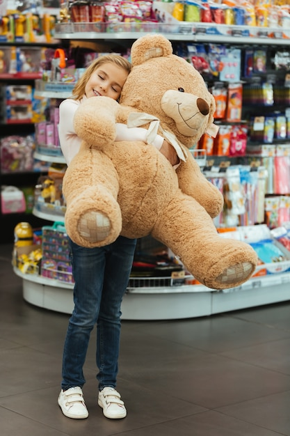 Delighted little girl holding big teddy bear Free Photo
