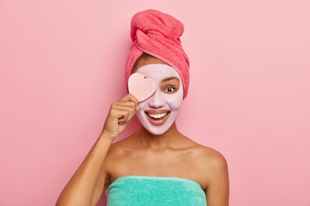 Delighted pleased female model holds cosmetic sponge, applies facial clay mask which suits her skin, has cosmetic procedures in bathroom Free Photo