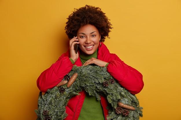 喜んでいる女性は携帯電話で電話をかけ、クリスマスイブにお祝いの気分を味わい、最新のニュースを伝え、松ぼっくりのトウヒの花輪を運び、黄色い壁に広く孤立した笑顔を見せます。 無料写真