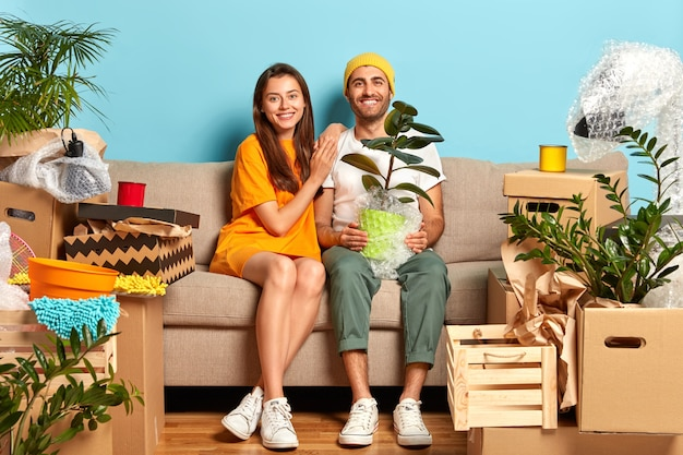 Delighted young couple sitting on the couch surrounded by boxes Free Photo