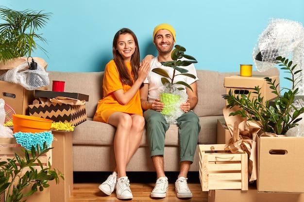 Довольная молодая пара сидит на диване в окружении коробок Бесплатные Фотографии