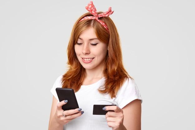 Восхитительная молодая лисица с haedband, одетая в повседневную белую футболку, держит современный сотовый телефон и кредитную карту, делает платеж онлайн, подключен к беспроводному интернету, изолирован на белой стене Бесплатные Фотографии