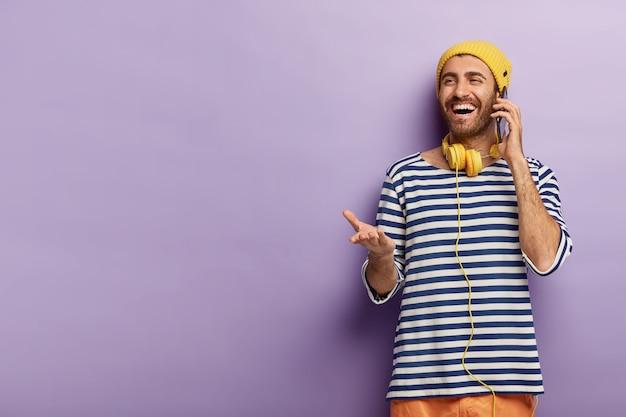 喜んでいる若い男はスマートフォンで手配し、携帯電話で話し、手のひらを上げ、嬉しい表情をし、縞模様のジャンパーを着ています 無料写真