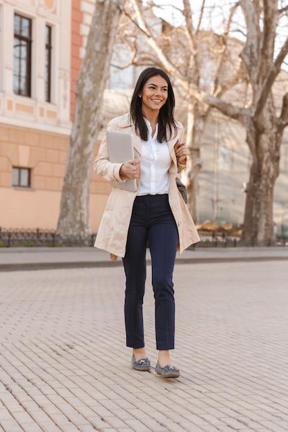 秋のコートに身を包んだ喜んで若い女性 Premium写真