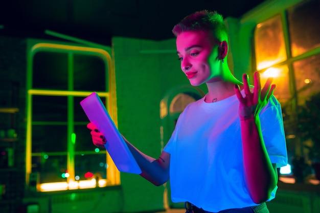 Delizioso. ritratto cinematografico di donna alla moda in interni illuminati al neon. tonica come effetti cinematografici, colori luminosi al neon. modello caucasico utilizzando tablet in luci colorate al chiuso. cultura giovanile. Foto Gratuite