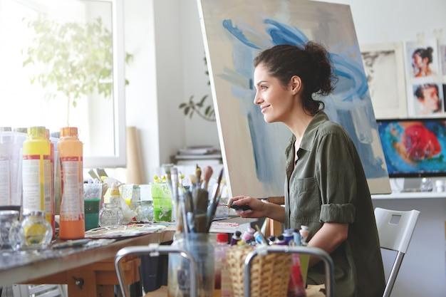 Восхитительная самка одета небрежно, смотрит в окно, наслаждается солнечным светом, работая в своей мастерской, создавая прекрасные картины, рисуя разноцветными маслами. женщина-художник рисует на холсте Бесплатные Фотографии