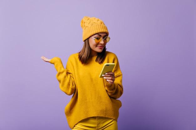 Очаровательная приятная студентка из европы с удивлением смотрит в свой телефон смс. девушка в желтой теплой шляпе и разноцветных очках позирует для изолированного портрета Бесплатные Фотографии