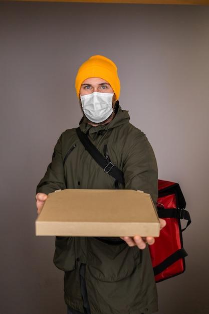 ピザが入った紙箱を扱うフェイスメディカルマスクを身に着けている男性を配達し、戸口の貸衣装に渡す 無料写真