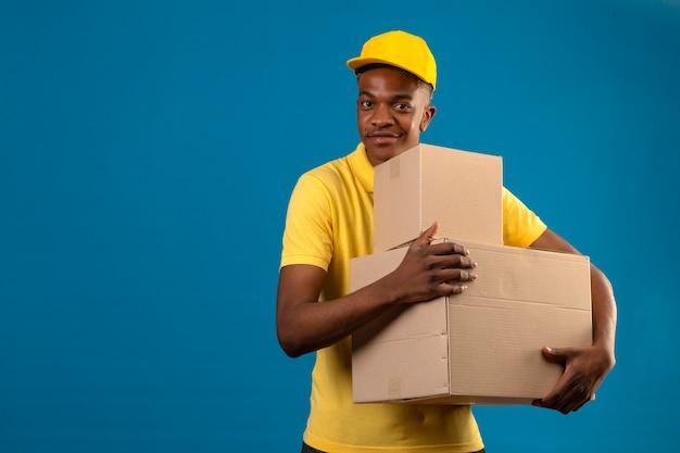 Афро-американский мужчина доставки в желтой рубашке поло и кепке держит картонные коробки с дружелюбной улыбкой, стоя на изолированном синем Бесплатные Фотографии