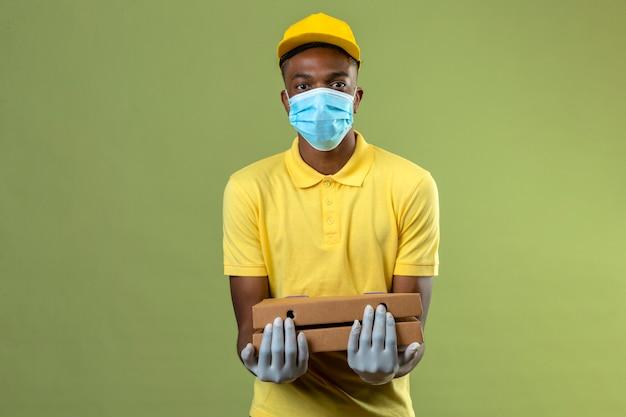 Consegna uomo afroamericano in maglietta polo gialla e berretto indossando maschera protettiva medica che tiene scatole per pizza con faccia seria in piedi sul verde Foto Gratuite