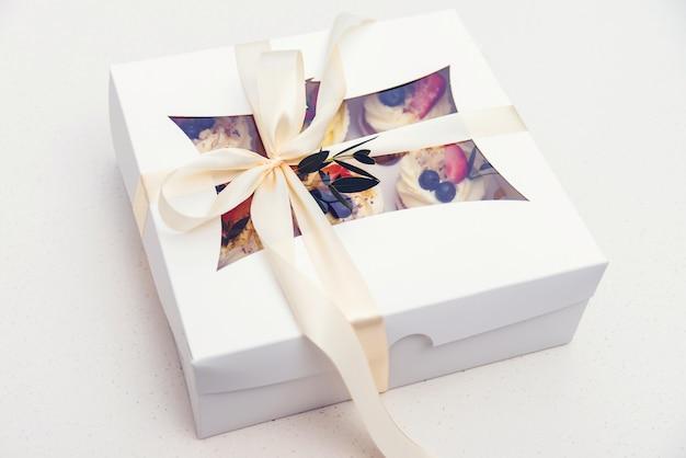 Коробка с доставкой вкусных кексов. бумажная коробка с фруктовыми кексами. празднование дня матери. день рождения. пасхальные праздники отмечают. Premium Фотографии