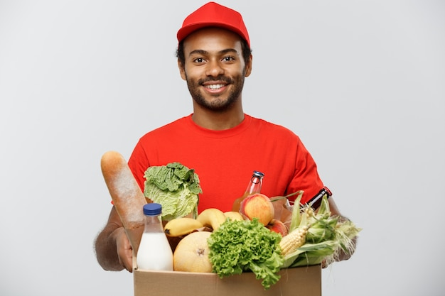Delivery concept - handsome african american delivery man carrying package box of grocery food and drink from store. isolated on grey studio background. copy space. Free Photo