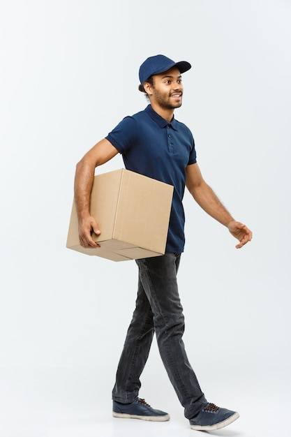 Delivery concept - handsome african american delivery man. isolated on grey studio background. copy space. Free Photo