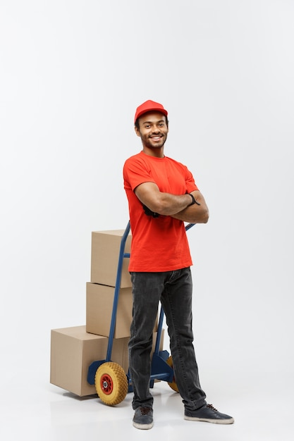 Delivery concept - portrait of handsome african american delivery man or courier pushing hand truck with stack of boxes. isolated on grey studio background. copy space. Free Photo