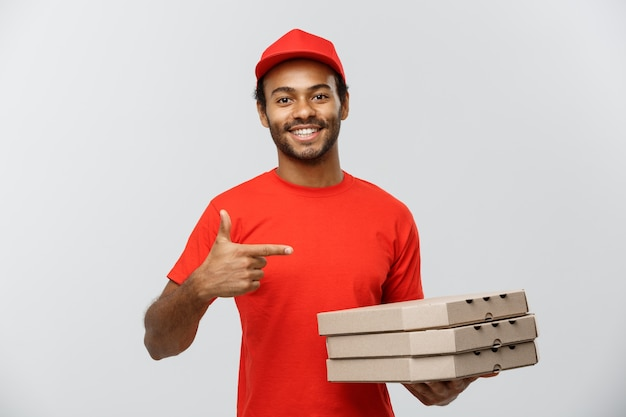 Delivery concept - portrait of handsome african american pizza delivery man. isolated on grey studio background. copy space. Free Photo