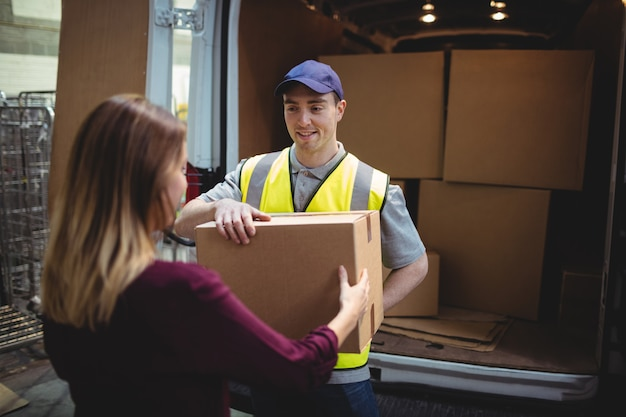 Delivery driver handing parcel to customer outside van in warehouse Premium Photo