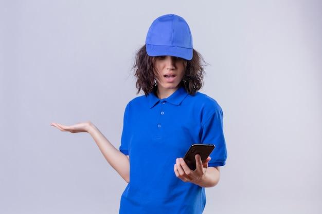 Ragazza delle consegne in uniforme blu e cappuccio guardando il telefono cellulare con espressione confusa in piedi con il braccio alzato su bianco Foto Gratuite