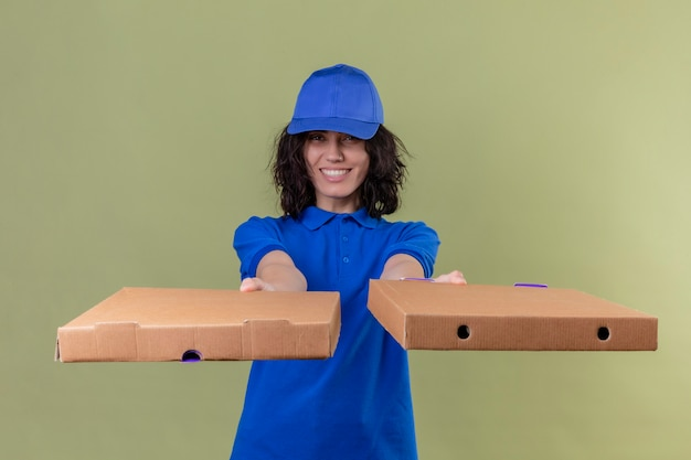Delivery girl in blue uniform and cap stretching out pizza boxes smiling friendly with happy face standing over isolated olive color space Free Photo