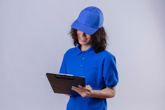 自信を持って立っている笑顔でそれを見てクリップボードを保持している青い制服とキャップを保持している配達の女の子 無料写真