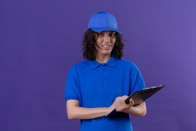 青い制服を着た配達の女の子とフレンドリーな笑顔の立っているキャップを保持しているクリップボード 無料写真
