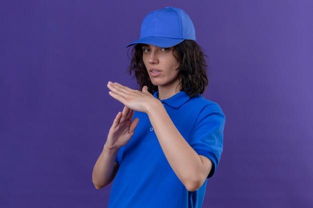 Доставщица в синей форме и кепке смотрит на работу, делая жест тайм-аута руками на изолированном фиолетовом Бесплатные Фотографии