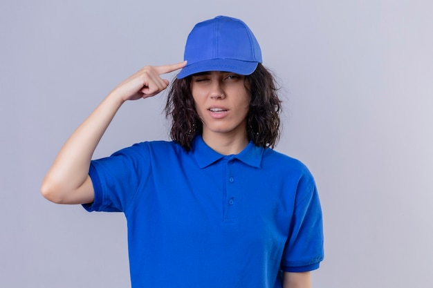青い制服を着た配達少女と指の思考でキャップを指す寺院は、立っているタスクに焦点を当てています 無料写真
