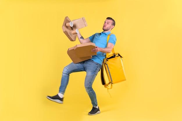 Разносчик в синей форме поскользнулся, потерял равновесие и бросил коробки с едой из ресторана в сторону. Premium Фотографии