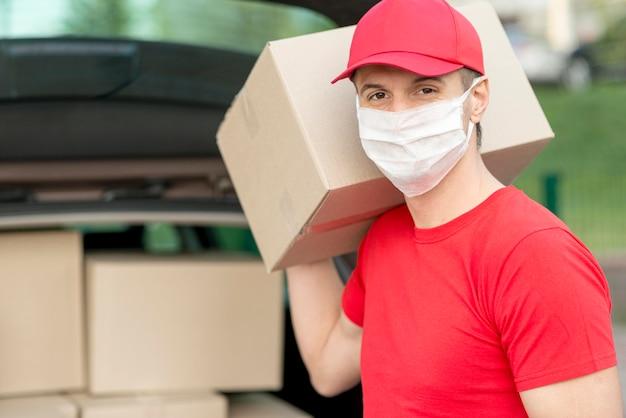 Парень доставки в маске держит коробку Premium Фотографии