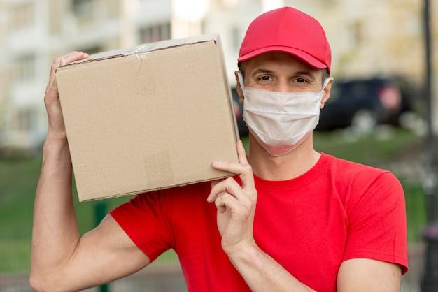 Доставка парень в хирургической маске Premium Фотографии