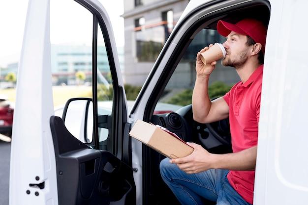 Uomo di consegna in auto a bere il caffè Foto Gratuite