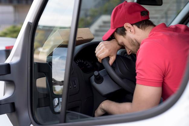 Uomo di consegna in auto stanco Foto Gratuite