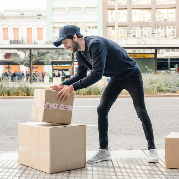 Delivery man carrying parcel near street Free Photo