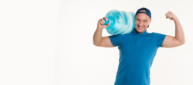Delivery man carrying water bottle and showing bicep Free Photo