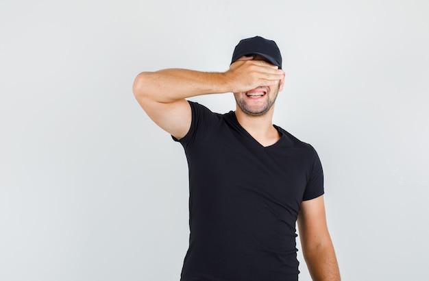 黒のtシャツ、キャップ、元気に見える手で目を覆っている配達人。 無料写真