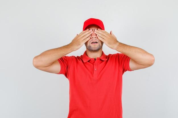 赤いtシャツで手で目を覆う配達人 無料写真