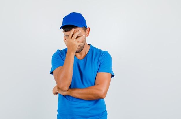 青いtシャツ、キャップで手で顔を覆い、物思いにふける配達人。 無料写真