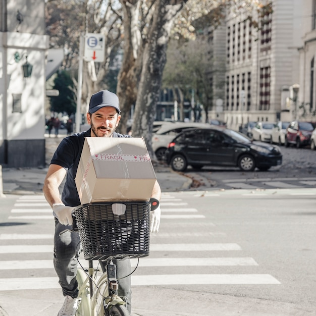 Delivery man crossing street on bicycle with parcel Free Photo