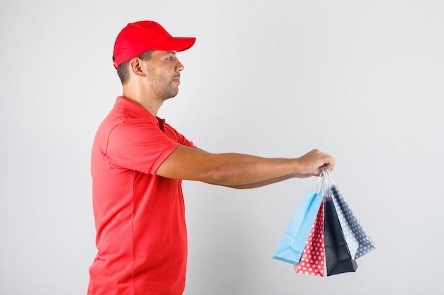 Курьер доставляет цветные бумажные пакеты в красной форме Бесплатные Фотографии