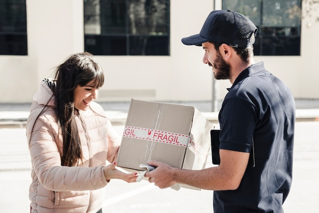 Delivery man delivering parcel to female customer Free Photo