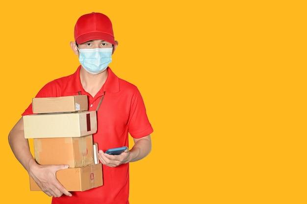配達人従業員キャップとシャツ赤い制服フェイスマスクホルダー小包 Premium写真