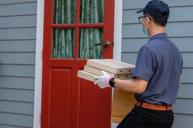Работник доставляющий покупки на дом в синей кепке, маске, униформе, маске и медицинских перчатках доставляет еду на вынос. служба доставки в условиях карантина, вспышки заболевания, пандемии коронавируса ковид-19. Premium Фотографии