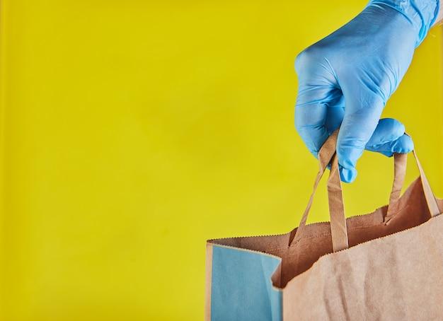 青い手袋の配達人の雇用主は、分離された食品とクラフトペーパーバッグを保持します。サービス検疫パンデミックコロナウイルスウイルスコンセプト2019-ncov。コピースペース。オンラインショッピング Premium写真