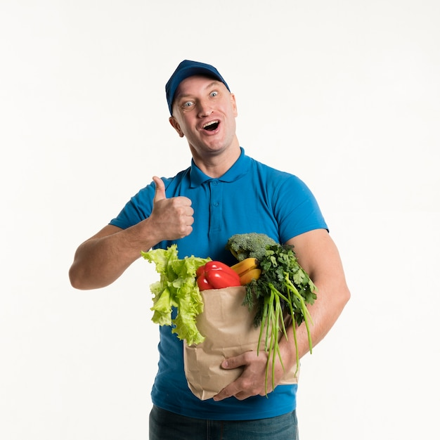 Delivery man giving thumbs up and holding grocery bag Free Photo